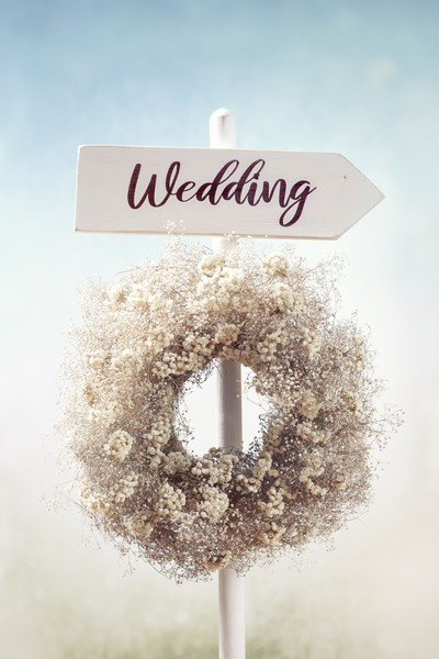 Rustic white wooden wedding directional sign and flower wreath in the garden.