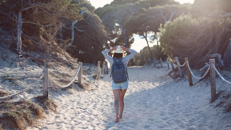Ilustrasi turis wanita di pantai (iStock)