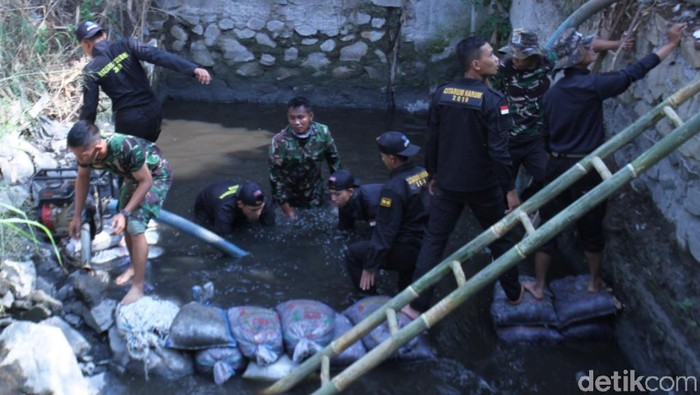 Personel Satgas Citarum Harum menutup lubang limbah yang mengotori Sungai Citarum. (Wisma Putra/detikcom)
