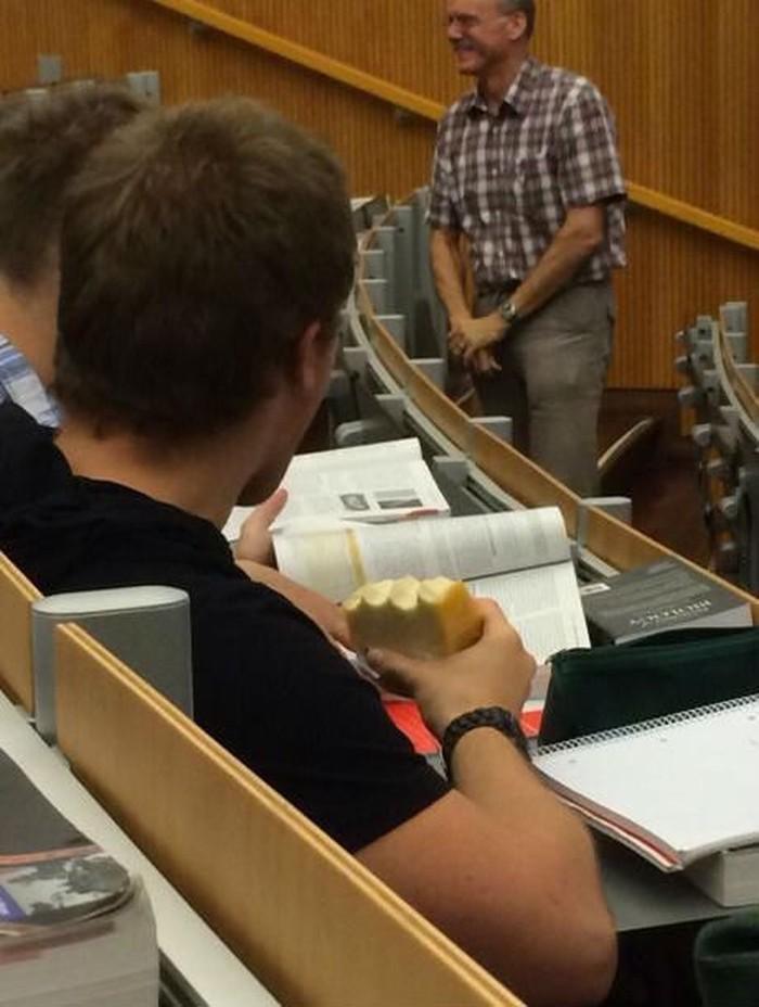 Perut lapar kala mendengar penjelasan dosen, mahasiswa ini diam-diam menyantap makanan yang dibawanya. Foto: Istimewa