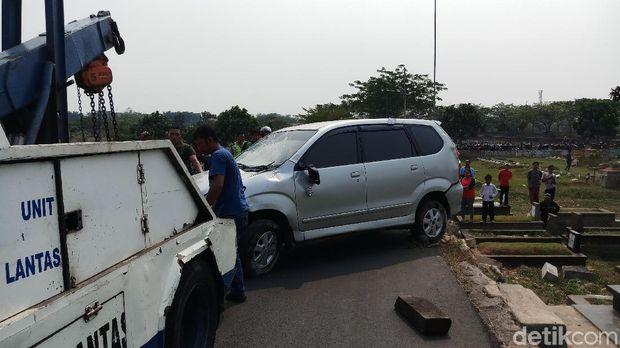 Mobil terguling dan menimpa makam di TPU Tanah Kusir, dievakuasi, Jumat (6/9/2019)