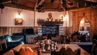 Interior dalamnya dibuat dari kayu dengan gaya rumah jadul yang nyaman. Ada sofa yang menghadap langsung kke perapian (The Groundskeepers Cottage)