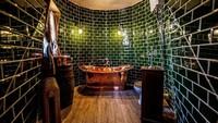 Walau tak begitu mirip, tapi kamar mandinya tetap dibuat dengan nuansa Harry Potter. Bathtub dibalut warna emas yang cantik (The Groundskeepers Cottage)