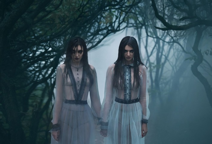 The girls are crying. Young ladies in ancient dresses walking through the woods in search of a victim. Foggy, spooky forest. Photoshoot in the style of horror. Mystical photo. Fashionable tinted.Creative color.