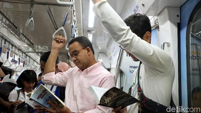 Anies Baswedan membaca buku di MRT. (Rengga Sancaya/detikcom)