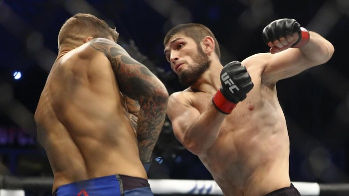 Russian UFC fighter Khabib Nurmagomedov, right, fights with UFC fighter Dustin Poirier, of Lafayette, La., during Lightweight title mixed martial arts bout at UFC 242, in Yas Mall in Abu Dhabi, United Arab Emirates, Saturday , Sept.7 2019. (AP Photo/ Mahmoud Khaled)
