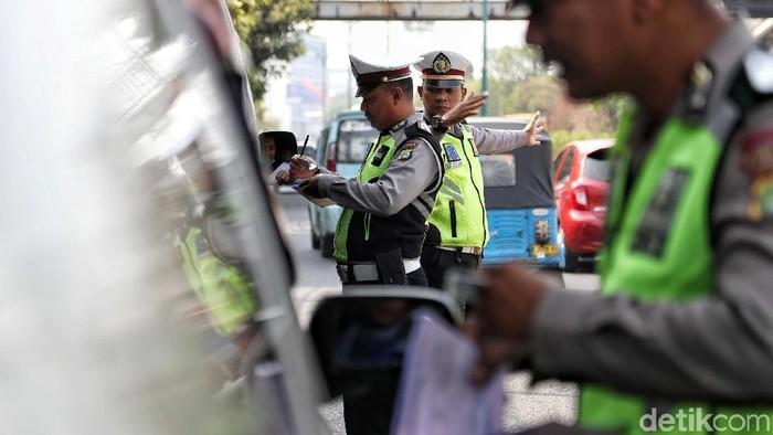 Sejumlah petugas Polisi Lalu Lintas (Polantas) melakukan tindakan penilaian terhadap mobil berplat genap di kawasan perluasan jalan ganjil genap,  Simpang Besar Matraman,  Jakarta,  Senin (9/9).  Penindakan tilang tersebut mulai diberlakukan pada hari ini (9/9) setelah pihak Kepolisian dan Dishub  melakukan sosialisasi perluasan rasa jalan ganjil genap selama satu bulan. Masih banyak mobil yang ditilang pada hari ini dengan alasan tidak mengetahui perluasan ruas jalan ganjil genap.