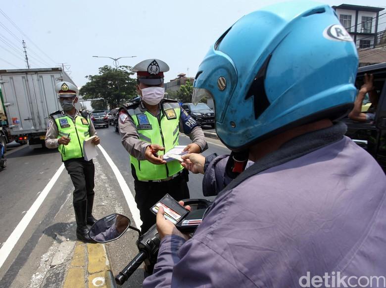 Sejumlah penegndara tengah mengantre untuk dikenakan sangsi tilang oleh kepolisian di Fly Over Pesing, Jakarta Barat, Senin (9/9/2019). Meski telah terpasang rambu-rambu para pengendara tetap nekat melanggar.