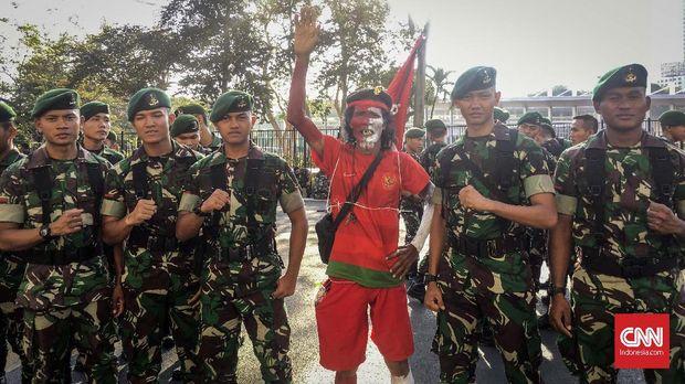Pendukung Indonesia Muhammad Kurniawan di tengah petugas keamanan unsur TNI di GBK. (