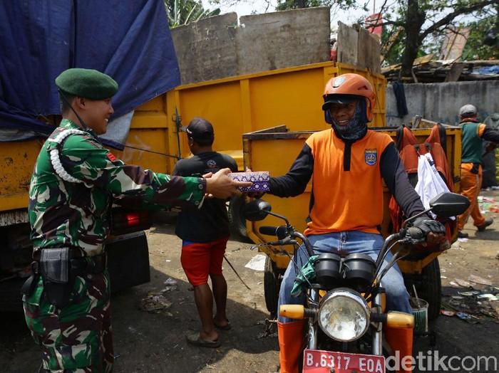 Petugas TNI Divisi 1 Kostrad Cilodong bersama Persit menjalani program Jumat Berkah. Mereka membagikan makanan kepada petugas kebersihan.