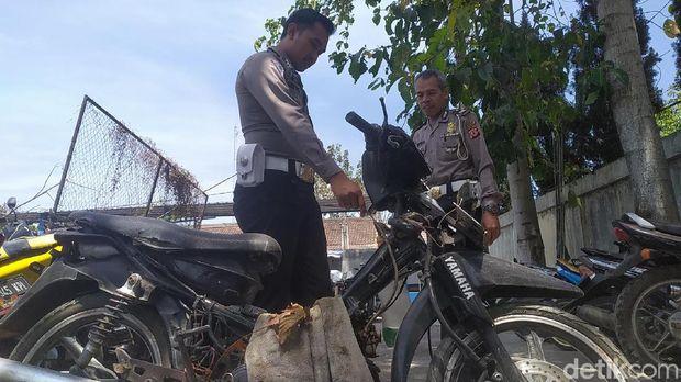 Polisi mengecek motor dengan tangki dari botol