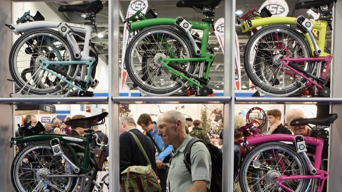 LONDON, ENGLAND - JANUARY 13:  A man views the Brompton folding bikes on display at the London Bike Show at the ExCeL centre on January 13, 2011 in London, England. The bicycle trade show, which runs until January 16, 2011, features over 60 stands displaying of all types of bikes as well as clothing and bike accessories.  (Photo by Oli Scarff/Getty Images)