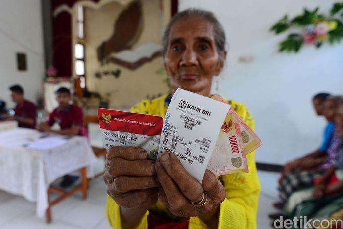 Warga Rote menunjukan bantuan Program Keluarga Harapan (PKH) yang baru diterimanya. Pencairan dana PKH itu dilakukannya di Bank BRI terdekat.
