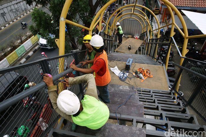 Pekerja tengah melakukan pembangunan Jembatan Penyebrangan Orang (JPO) Pasar Minggu, Jakarta Selatan, Selasa (17/9/2019).