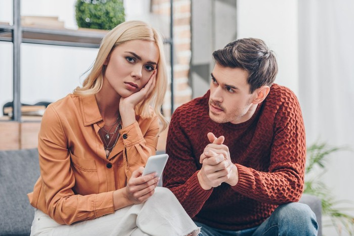 husband looking at unhappy young woman holding smartphone and looking at camera at home, relationship problem concept