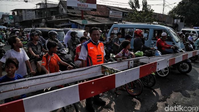 Petugas KAI Daop 1 Jakarta melakukan sosialisasi keselamatan berlalu lintas di perlintasan sebidang Bukit Duri Manggarai, Jakarta, Selasa (17/9). Dengan sosialisasi tersebut, diharapkan kesadaran masyarakat untuk menaati aturan lalu lintas di perlintasan sebidang semakin meningkat.