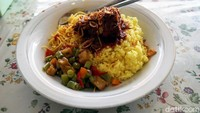 Dalam satu piring nasi kuning Banjar ini ada sayur kacang panjang dan kentang, mie kuning serta bawang goreng. Untuk lauknya, ada ikan tongkol dengan sambal yang cukup pedas. (Wahyu Setyo/detikcom)