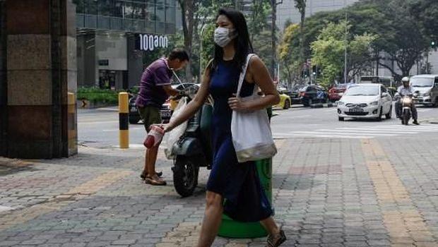 Penduduk singapura memakai masker untuk menghalau asap
