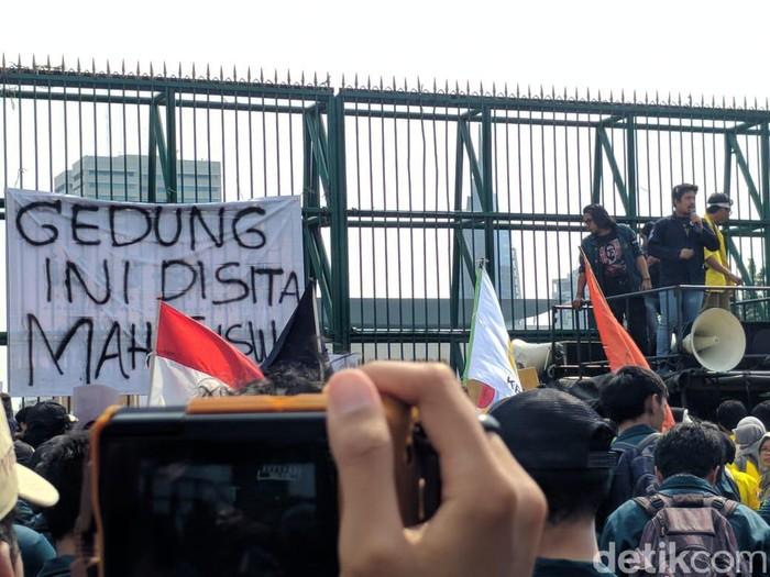 Mahasiswa pasang spanduk menyita gedung DPR saat demo menolak pengesahan RUU KUHP. (Jefrie Nandy/detikcom)