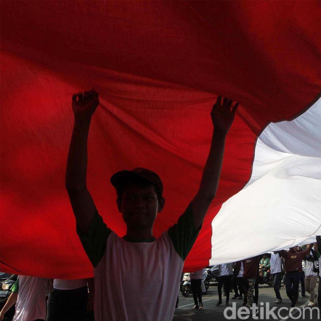 Potret Aksi Membentangkan Bendera Merah Putih Raksasa di Depan Istana