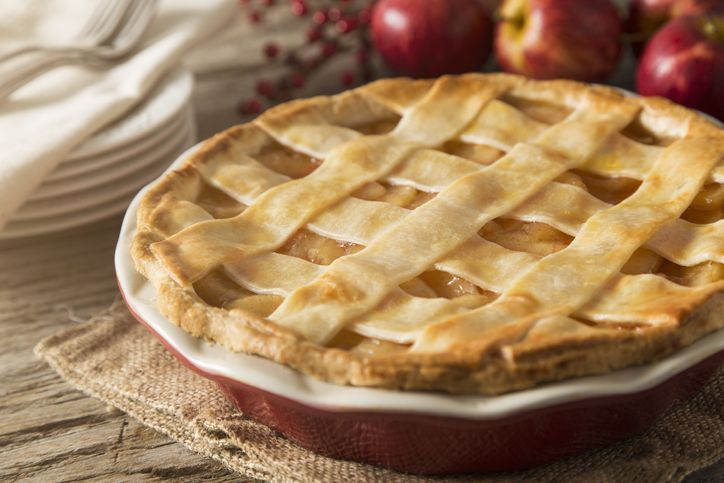 A top view of an apple pie with a slice removed on a white background.  The flaky, golden crust invites the viewer to reminisce.  The pie sits in a foil tin with one slice taken out leaving behind traces of the pie.  Pie filling just barely oozes out of the edges, leaving one to wonder who took the slice?