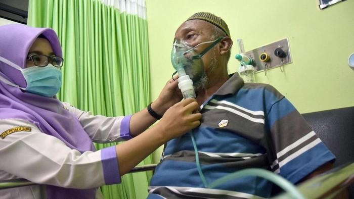 Sejumlah warga mendapatkan perawatan dengan alat nebulizer karena mengalami sesak napas di posko kesehatan. (Foto: Antara Foto)