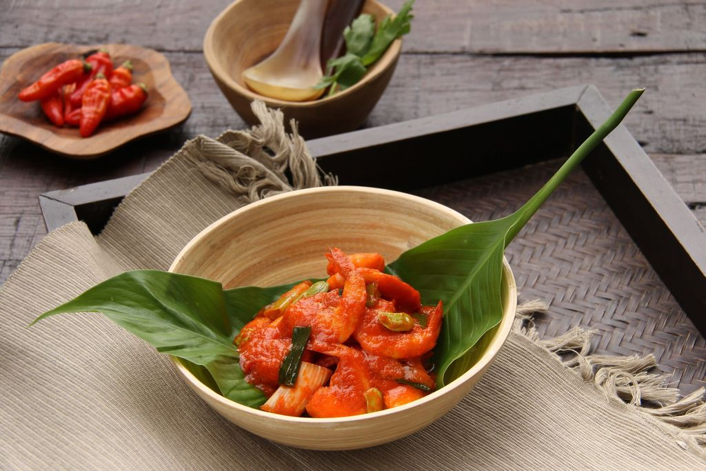 A popular dish of stir-fried shrimps in red chili paste from Padang, West Sumatra. Plated in a bamboo bowl lined with a broad green leaf. Arranged on a wooden tray that has been lined with casually-laid place mat. A small wooden saucer of red chili peppers and a wooden bowl of spoons are placed next to the tray. The dish is styled on a dark color, rustic wooden table.