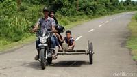 Seorang warga bersama anaknya menggunakan becak untuk melakukan kegiatan sehari-hari.