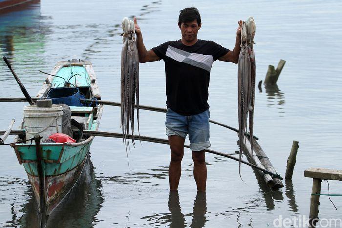 Seorang nelayan menunjukkan gurita hasil tangkapannya.