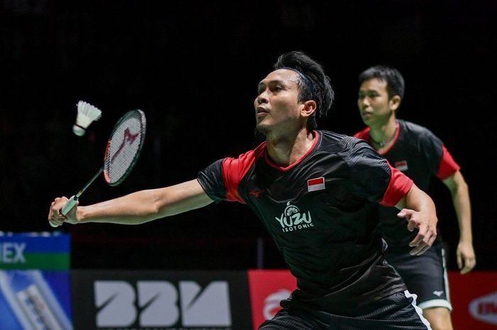 Indonesias Mohammad Ahsan (L), next to Indonesias Hendra Setiawan, returns a shuttlecock to Japans Yugo Kobayashi and Japans Takuro Hoki during of their mens doubles final game at the BWF Badminton World Championships at the St Jakobshalle in Basel on August 25, 2019. (Photo by FABRICE COFFRINI / AFP)