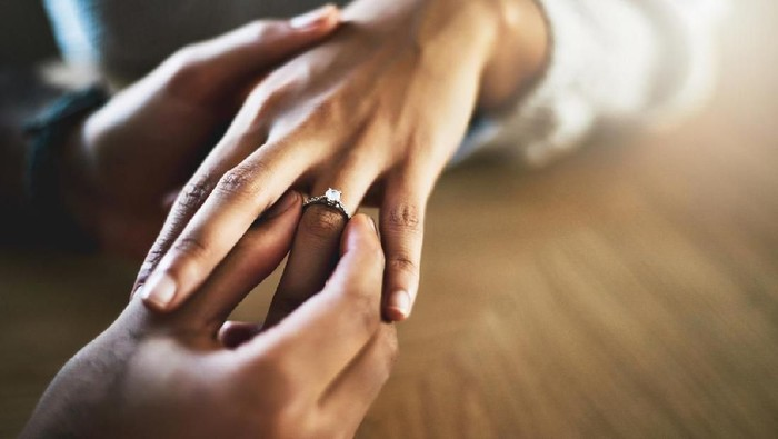 Cropped shot of a man putting an engagement ring onto his girlfriends finger