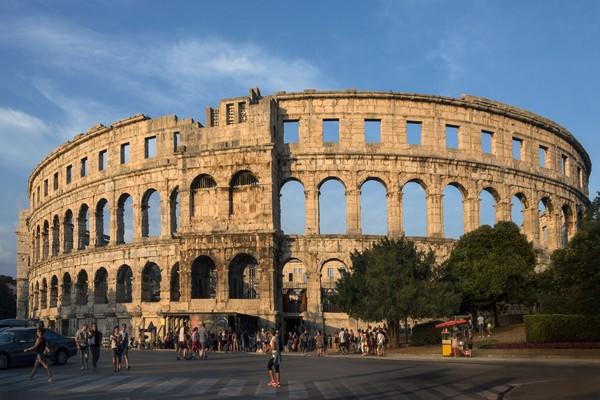 Bangunan yang dibangun pada 26 sebelum masehi tersebut bernama Pula Arena. Walau tidak identik, dua bangunan ini memang mirip. Kalau tidak ngeh, kamu bisa dengan mudah terkecoh. (iStock)