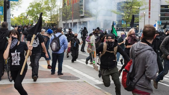 Seattle, WA, USA – May 1, 2015: Protesters run from gas grenades fired by Seattle police officers during May Day rioting on Capitol Hill.