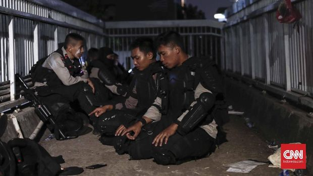 Aparat pun beristirahat dan beribadah saat mengawal demo mahasiswa, Selasa (24/9).