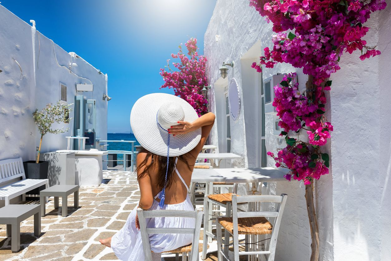 Elegant traveler woman enjoys the classic setting of white houses and colorful flowers on the cyclades islands of Greece during summer time