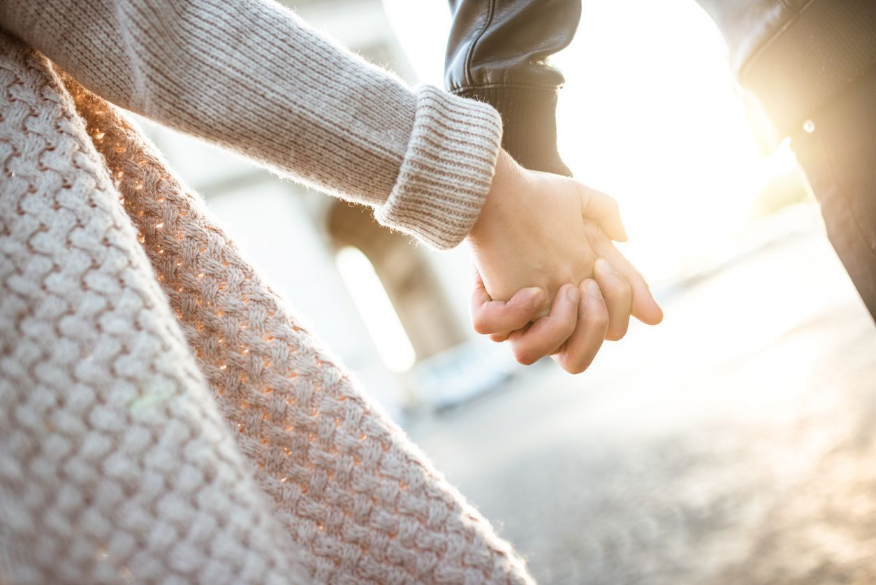 Close up of couple holding hands reconciled after quarrel, happy and relaxed about saved marriage. Husband and wife making peace avoiding break up. Concept of preserved relationship, family support