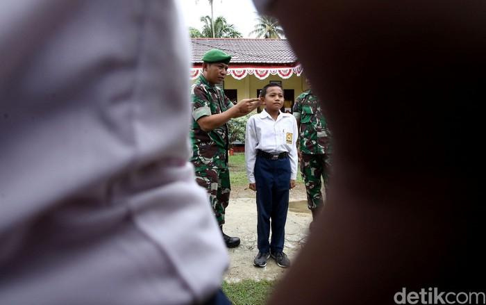 Sejumlah siswa SMP di Pulau Simeulue, Aceh, berbaris rapi dengan posisi sikap sempurna. Mereka mengikuti latihan baris berbaris yang diberikan oleh anggota TNI.