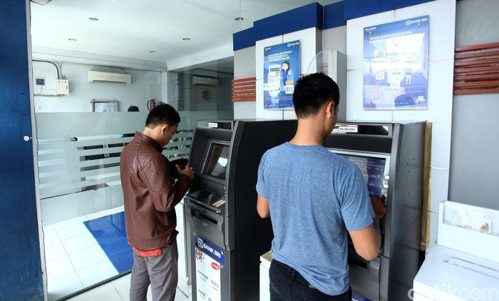 Sejumlah warga nampak menggunakan ATM yang berada di kawasan kantor unit Bank BRI di Sinabang, Pulau Simeulue, Aceh.
