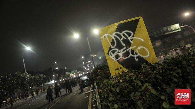 Coretan pada marka jalan mengkritik DPR yang ngebut mengesahkan sejumlah UU kontroversial.