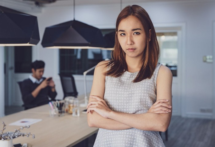 Women standing angry with laziness coworker at office