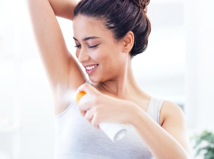 Shot of a young woman spraying herself with deodorant