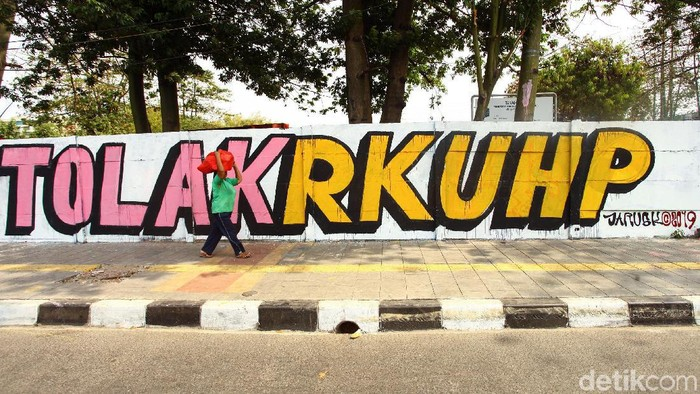 Ada pemandangan menarik saat melintasi Jalan Pemuda, Rawamangun, Jakarta Timur. Mural menolak RKUHP menghiasi dinding jalan itu.