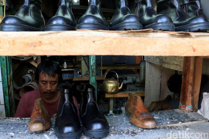 Seorang perajin alas kaki nampak sibuk menyelesaikan pembuatan sandal di rumah produksi sepatu Cibaduyut yang berada di Kecamatan Bojongloa Kidul, Kota Bandung.
