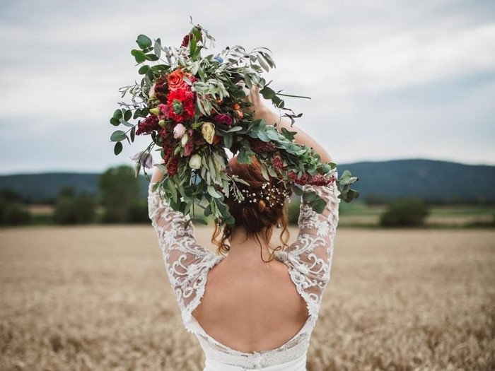 Stunning young bride with bouquet of wedding flowers standing in the wheat field