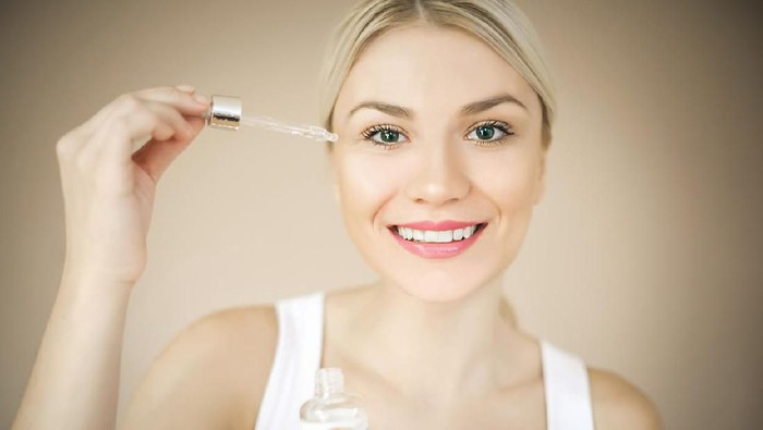 Woman with elegant makeup applying serum treatment. Space for copy.