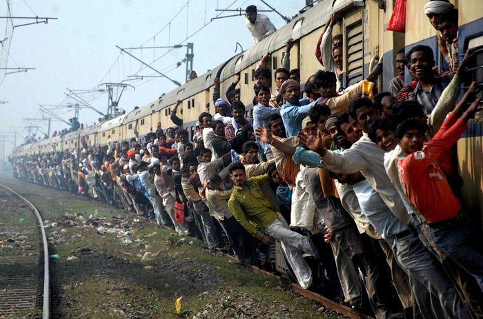 Ini adalah pemandangan penumpang kereta api yang telah cukup lama bertahan di negara tersebut. Banyak penumpang yang berusaha naik meski telah melebihi kapasitas kerea api.