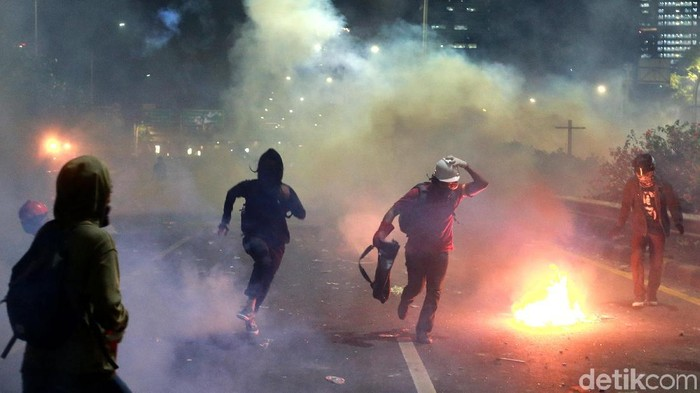 Pendemo bertahan dari asap dan gas air mata saat berunjukrasa di depan Gedung DPR RI. ( Foto: Muhammad Ridho)