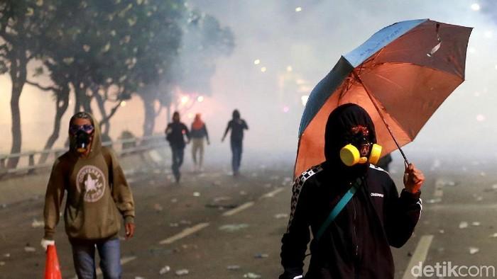 Para pendemo bertahan dari asap dan gas air mata saat berunjukrasa di depan Gedung DPR RI, Jakarta. Inilah potret massa yang berdiri paling depan.