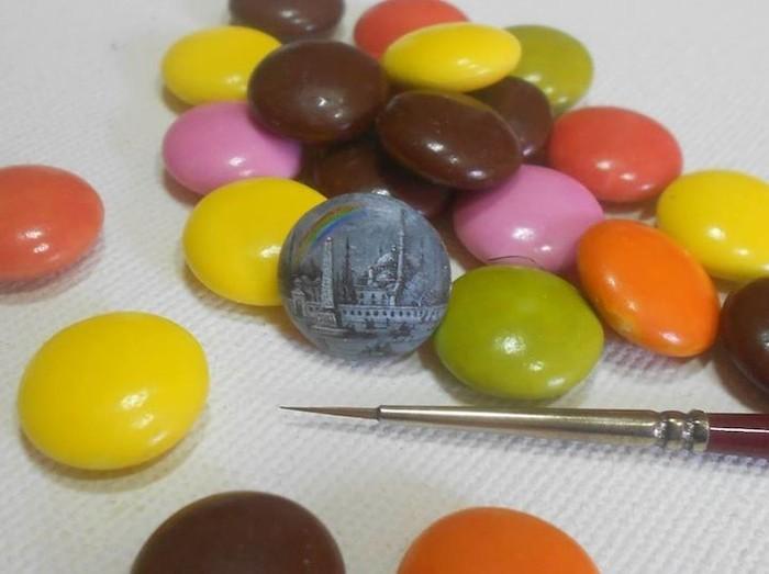 Adalah Hasan Kale yang mampu melukis di atas permukaan makanan yang mungil. Seperti pada lukisannya yang menggambarkan bangunan di atas permen cokelat ini. Foto: Hasan Kale