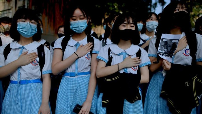 Schoolmates of form five student Tsang Chi-kin, 18, who was shot in the chest by police during violent pro-democracy protests that coincided with Chinas October 1 National Day, place their hands on their chests during a protest at a school in Hong Kong on October 2, 2019. - Hundreds of Hong Kongers staged a sit-in on October 2 outside the school of a protester who was shot by police as authorities said the wounded 18-year-old was now in a stable condition. (Photo by Mohd RASFAN / AFP)